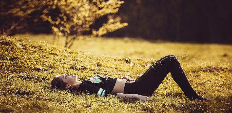 Frau liegt auf der Wiese