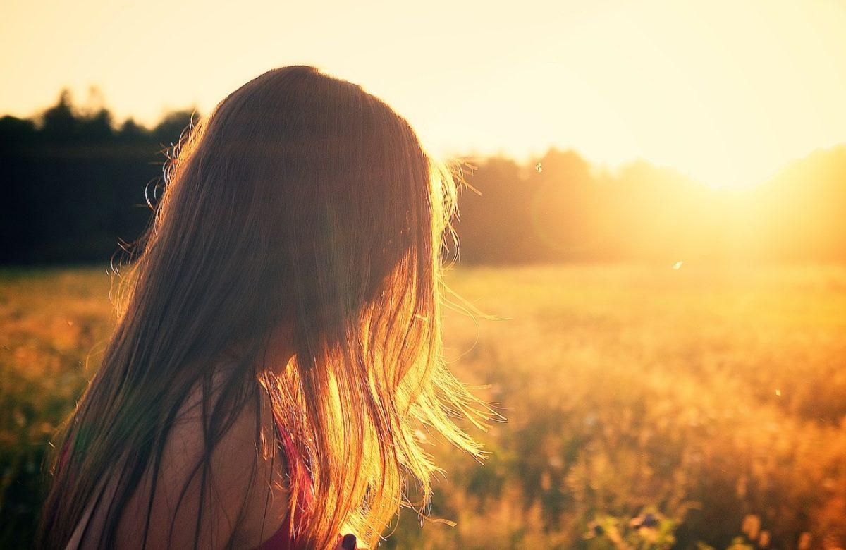 Frau vor der untergehenden Sonne